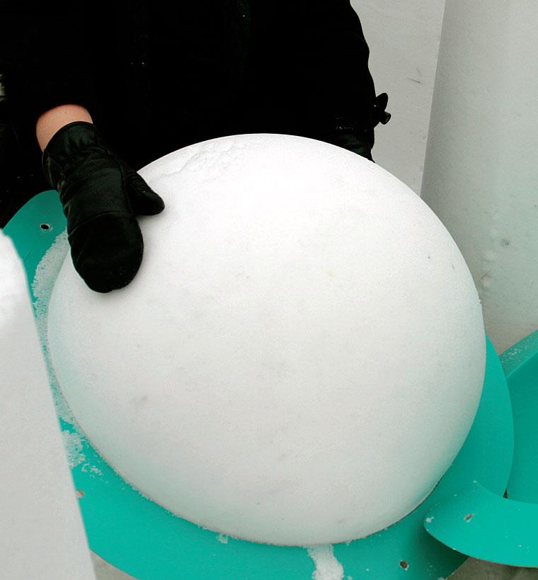 Suurta lumipalloa oli vaikea käsitellä. Sisäänkäynnin pylväiden päälle nostettuna se näytti liian suurelta, joten veistimme sille uuden, terävän muodon.