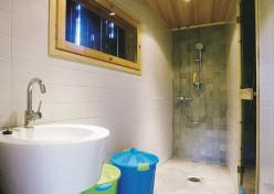 Suihkuhuoneen lattialaatoitus jatkuu tilan peräseinälle nousten. Seinälle nouseva lattialaatoitus korostaa osaltaan huoneen syvyyttä.