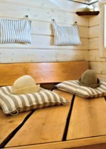 Uma ompeli saunaan pellavaiset tyynyt seinille ja lauteille.