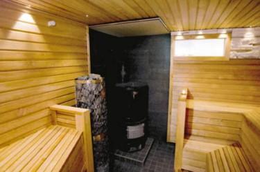Saunan ilme on luotu yhdistämällä kahta tervaleppäpaneelia ja vaaleaa koristekiveä. Lauteet on jaettu tilan kahdelle puolelle.