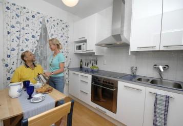 Sinivalkoinen keittiö näyttää avarammalta vaaleiden pintojen vuoksi