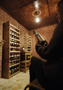 Viinipullotelineet koottiin pöytätelineistä korkeiksi hyllyiksi, jotka ruuvattiin yläosastaan kiinni seinään