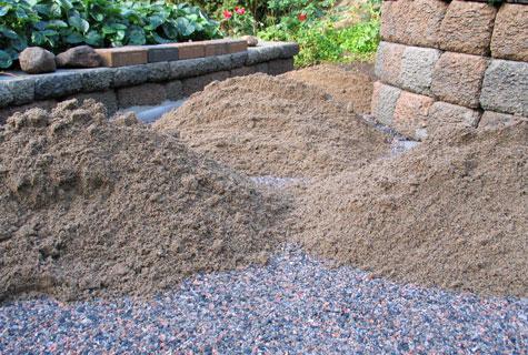 Kivimurskan päälle levitettävä asennushiekka odottaa levitystään. Tällä muutaman sentin kerroksella voidaan viimeistellä halutut kaadot ja se helpottaa merkittävästi kivien asennusta.
