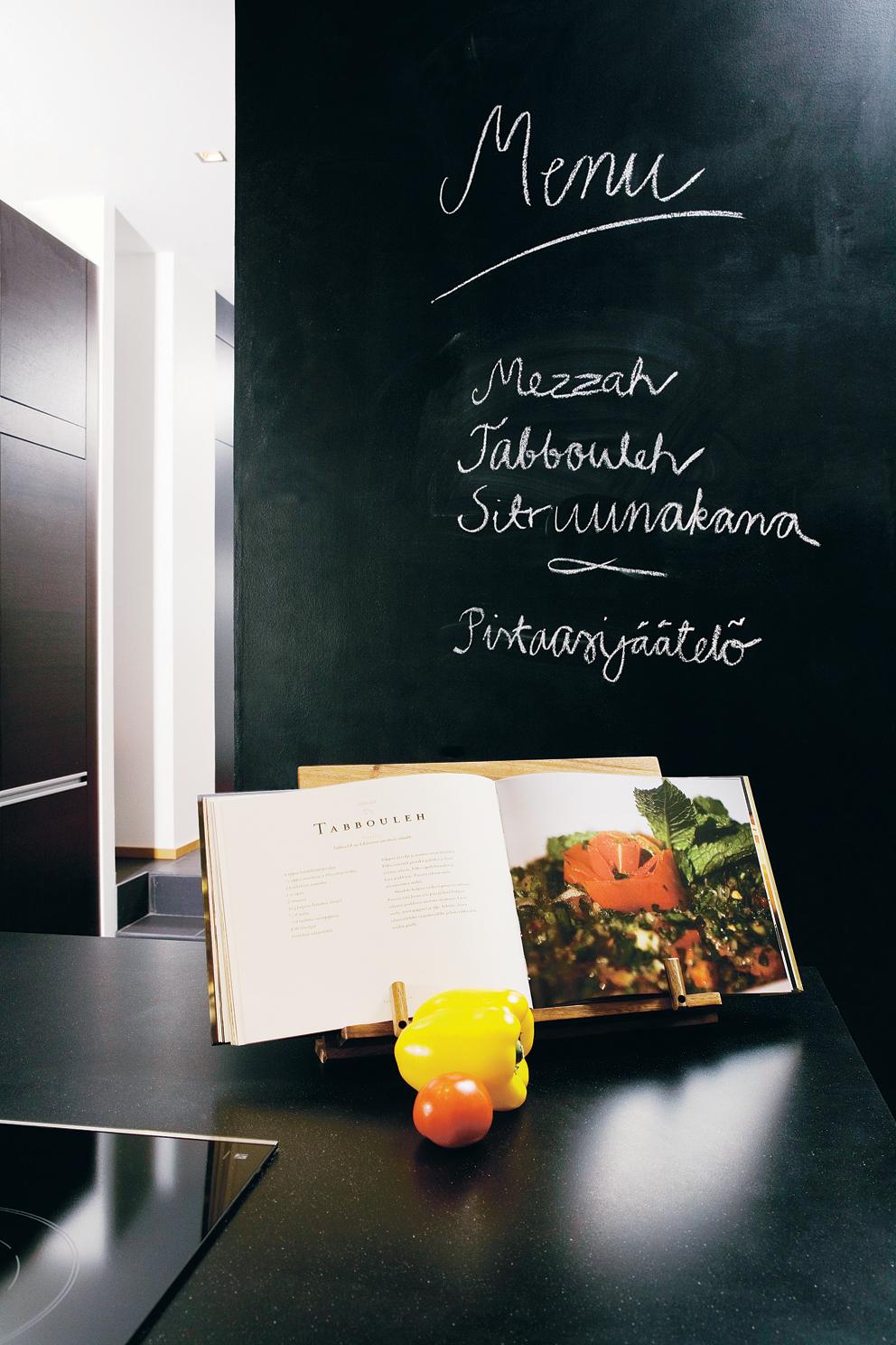 Hauska idea! Perheen äiti päätti maalata yhden keittiön seinistä mustaksi liitutaulumaalilla. Seinä toimii nyt perheen infopisteenä. Siihen on myös mukava kirjoittaa illan menu ruokavieraiden tutkittavaksi. Keittokirjateline Stockmannilta.