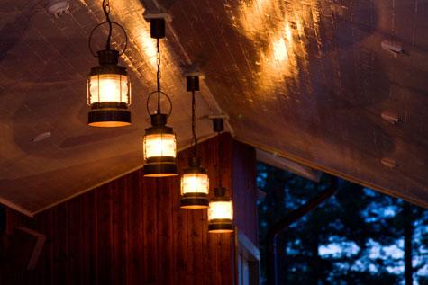 Rantasaunan terassi saa valoa tunnelmallisista riippuvalaisimista.