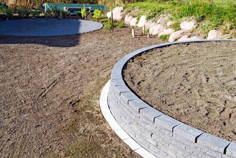 Matalan muurin edustalle on ladottu sauvakivirivi tulevan nurmikon leikkauksen helpottamiseksi.