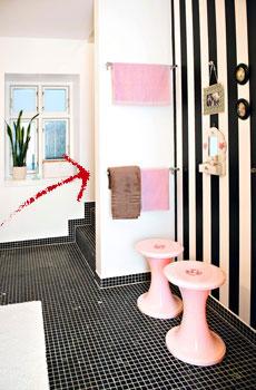 Raidallinen tapetti luo hotellimaista tuntua. Hauskoille vaaleanpunaisille jakkaroille voi istahtaa hetkeksi aamutoimien lomassa.