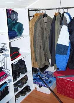 Päätyseinän pitkälle vaatetangolle mahtuu takki poikineen.