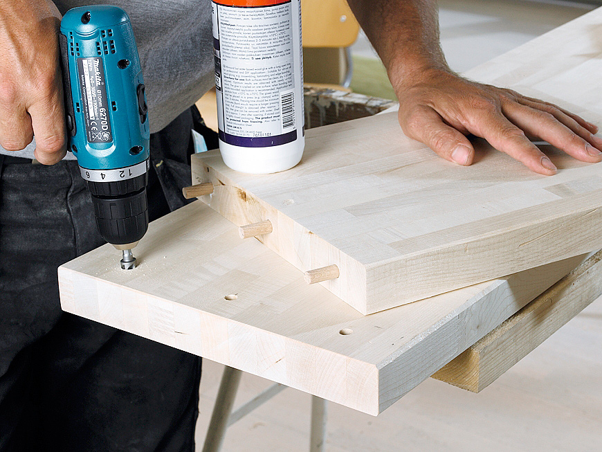 Yhdistä jalat ja taso. Reikiä kannattaa hiukan upottaa levyyn , jotta tapit saa helpommin paikoilleen. Tapit liimataan ensin jalkoihin ja sen jälkeen tasoon. Muista laittaa liimaa myös tasossa oleviin tapinreikiin.
