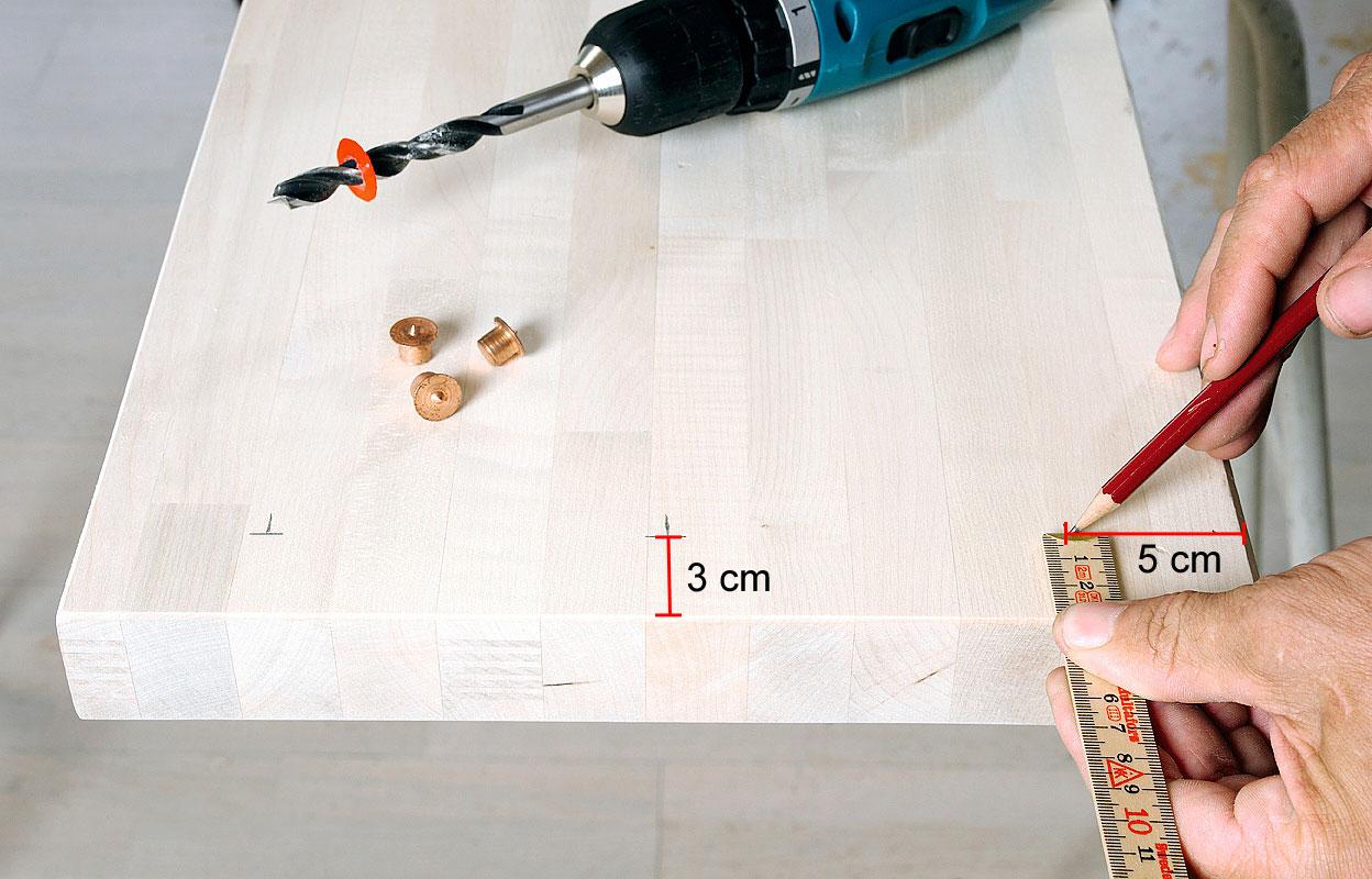 Mittaa tasoon kolmelle tapille paikat. Uloimmat tapit sijoitetaan 5 cm:n päähän reunasta molemmin puolin. Tämä puulevy on 4 cm paksu, joten tapit sijoitetaan 3 cm:n päähän päätyreunasta (puoli levyn paksuutta + 1 cm).