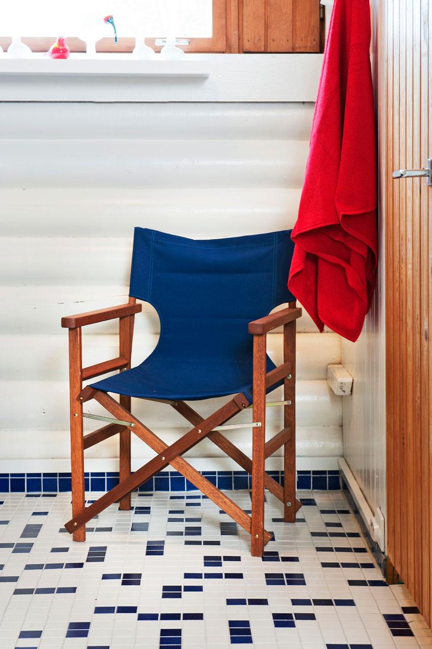 Pukuhuoneen lattiassa on kikkailtu sinisillä mosaiikkilaatoilla. Näkymä sopii rantamökin tunnelmaan ja tuo mieleen perheen veneilyharrastuksen.