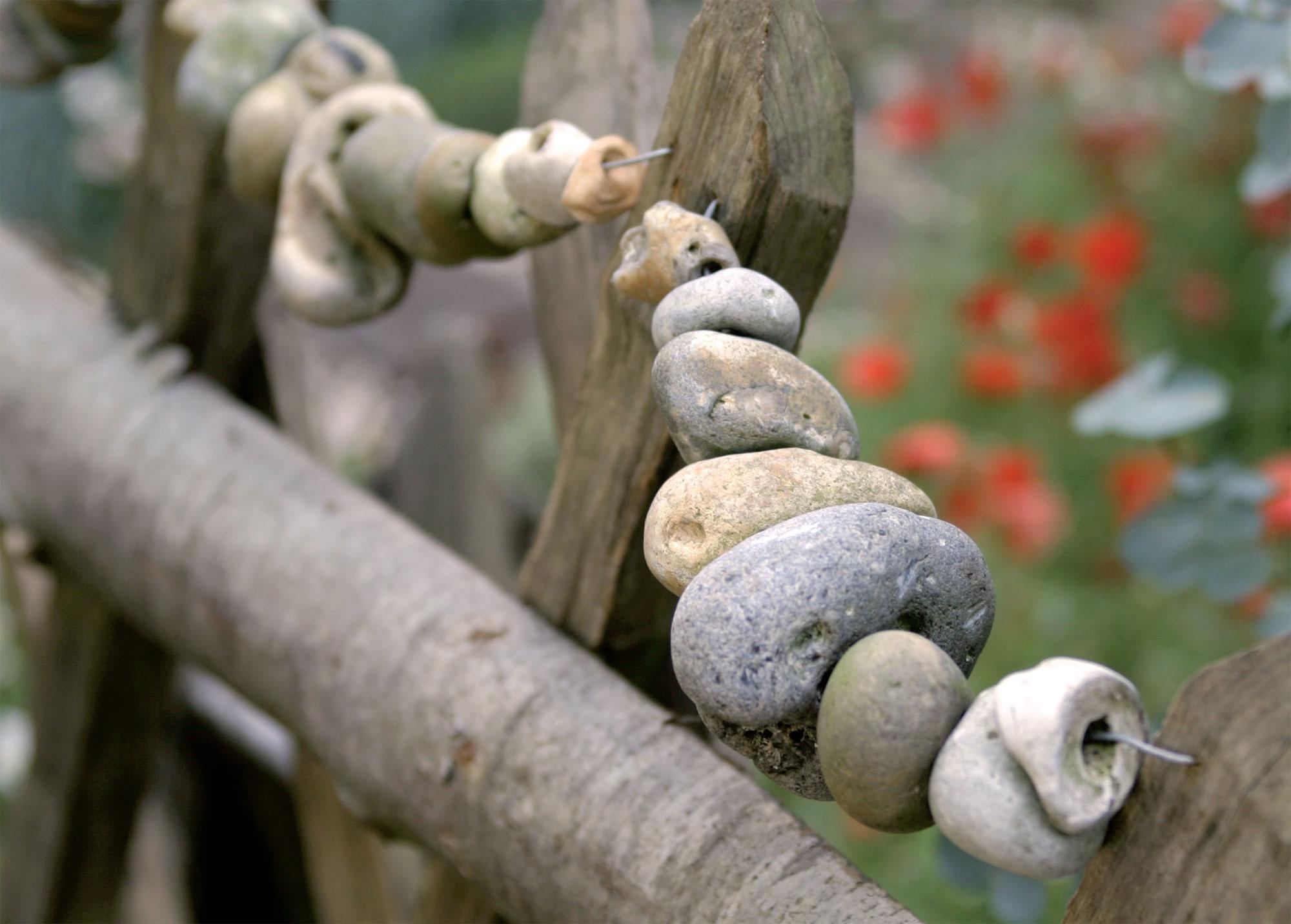 Tämä aita on somistettu rautalankaan pujotetuilla pienillä kivillä, joiden läpi on porattu reikä.