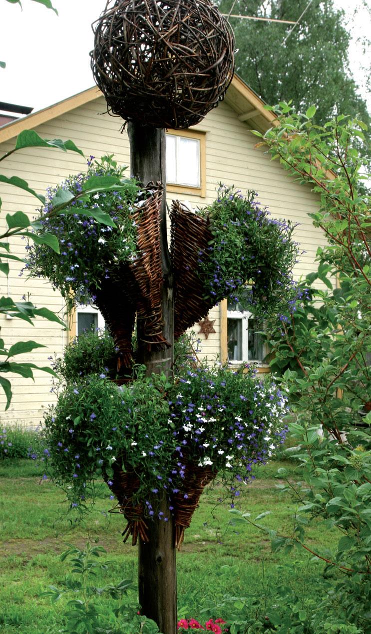 Tarjan heinäseipäästä ja pajupunoksista ideoima kukkapylväs on luonnonmukainen pihapatsas