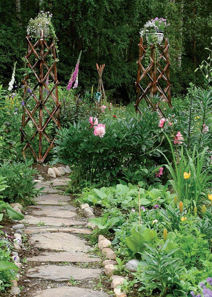 Puutarhan liuskekivikäytävä kulkee kukkapylväiden välistä.