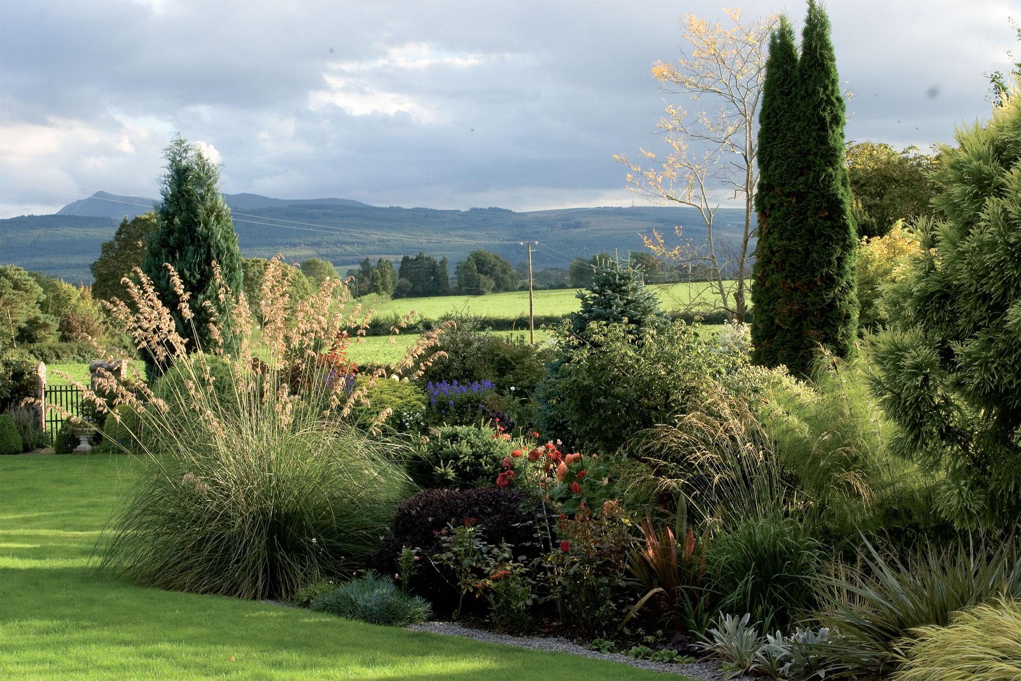 Näkymät laidunmaiden yli kohti Comeraghin vuoria on haluttu pitää avoimina, sillä näin puutarha luontevasti nivoutuu osaksi maisemaa. Stokesin perheen omistamille laitumille johtaa rautaportti puutarhan perältä. Etualalla komea jättihöyhenheinä (Stipa gigantea).