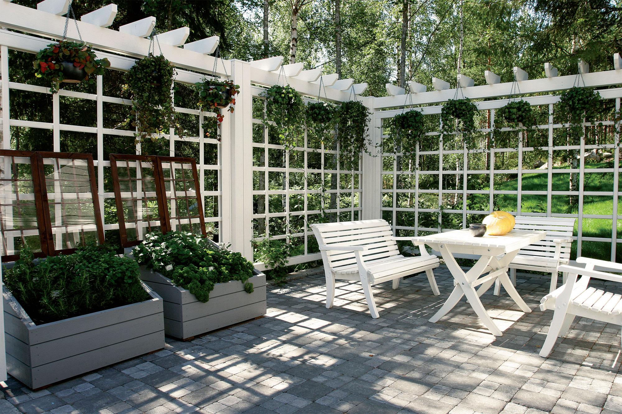 Talon vieressä oleva patio on rajattu ympäristöstä ilmavalla, pergolamaisella rakenteella. Seinäelementti kuuluu Kannustalon pihamallistoon, lisätietoja www.kannustalo.fi.
