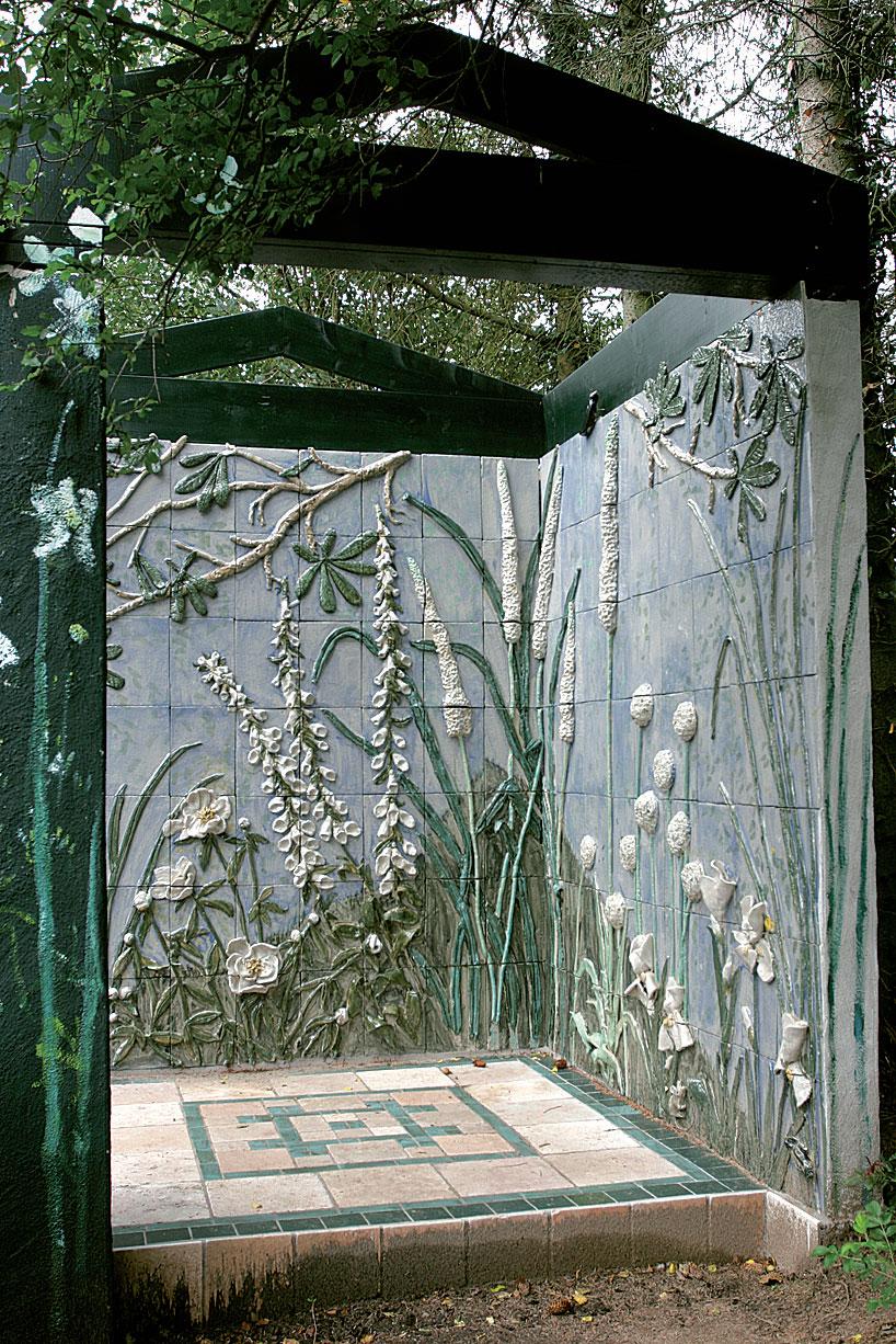 Keraamiset kukat elävät talvellakin seinämillä, jotka Anne on pystyttänyt puutarhaan. Päätykolmiot luovat tilaan huoneen tunnun.