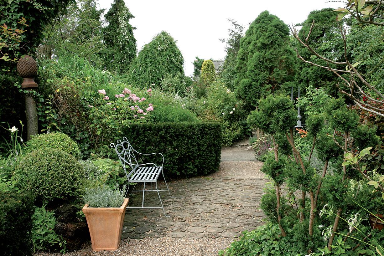 Oleskelupaikan avara kivipinta ja erimuotoisten kasvien harkittu vaihtelu tuovat tilaan kasvitieteellisen puutarhan ilmettä.