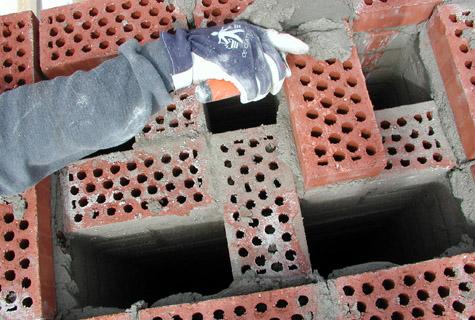 Savupiipun muuraus on ammattilaisen tehtävä. Osaava muurari selviää siitä yleensä muutamassa päivässä. Piippu voidaan muurata joko umpitiilestä tai reikätiilestä, ja siihen on helppo tehdä tarvittava määrä hormeja. Kuva: Wienerberger Oy.