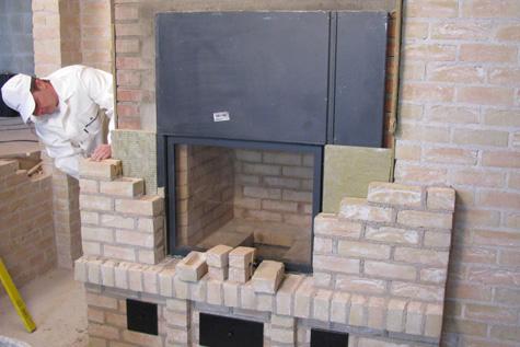 Tulisijan muuraus vaatii huolellisuutta. Tulipesän on kestettävä suurta kuumuutta, ja siksi se muurataan tulenkestävistä tiilistä erikoislaasteja käyttäen. Tulisijan ulkokuori eristetään muusta rakenteesta ohuella lämpöeristeellä, mikä tasaa rakenteen lämpötilanvaihteluja. Ulkokuori voidaan muurata tavallisista tiilistä. Kuva: Wienerberger Oy.